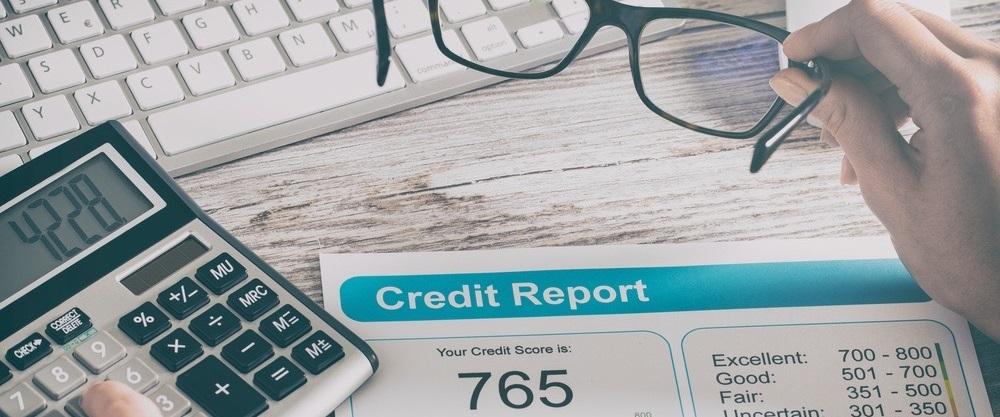 Человек подсчитывает свой кредитный статус на калькуляторе