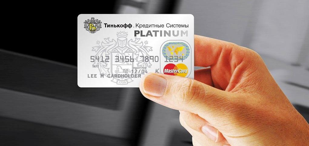 Девушка держит в руках карту банка Тинькофф