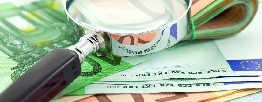 Лупа лежит на пачке евро