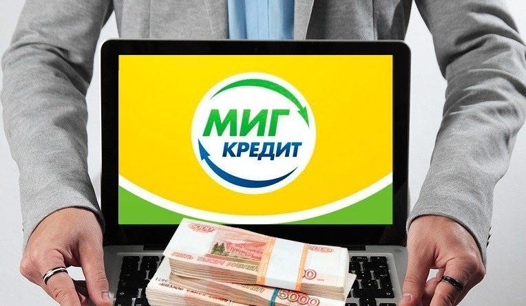 Мужчина держит ноутбук, на нем лежат деньги