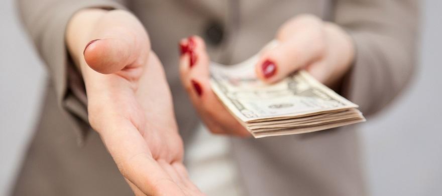 Девушка выдает наличные в качестве оплаты труда