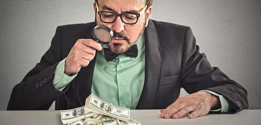 Мужчина в деловом костюме рассматривает через лупу доллары