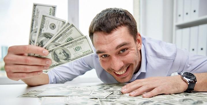 Человек счастлив от того, что держит в руках долларовые купюры