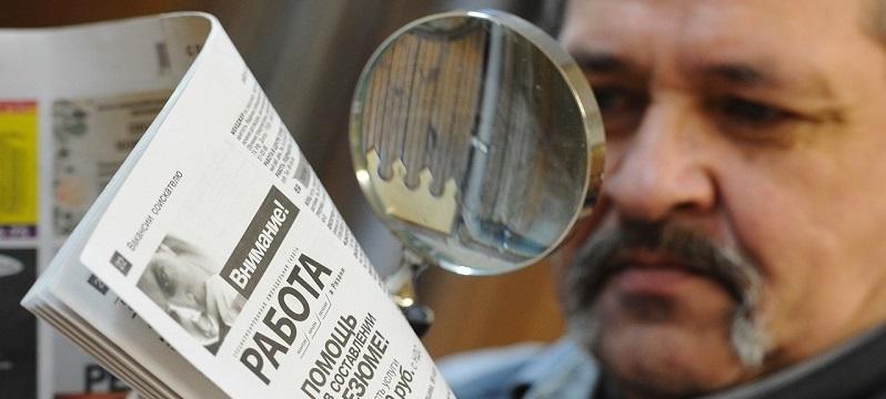 Безработный мужчина изучает газету с вакансиями