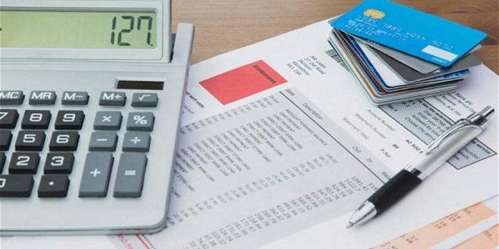 Отчет лежит на столе с ручкой, калькулятором и стопкой кредитных карт