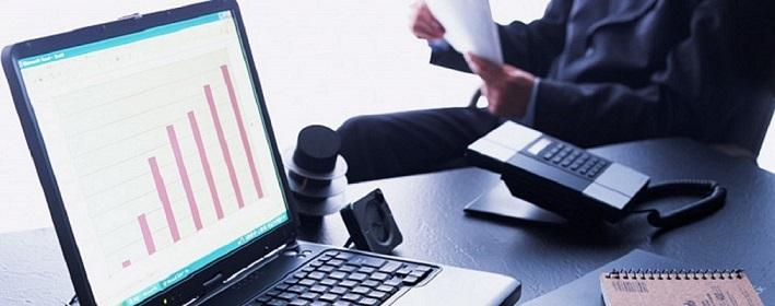 Открытый ноутбук с графиками роста и мужчина, изучающий документы