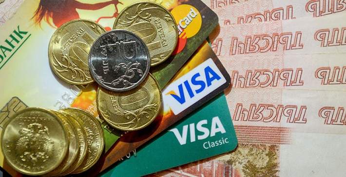 Карты Виза и железные деньги лежат на пятитысячных купюрах
