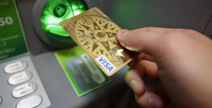 Человек вставляет кредитку в банкомат