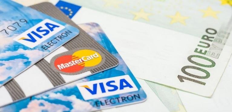 Карты Виза и Мастеркард лежат на купюре в 100 евро