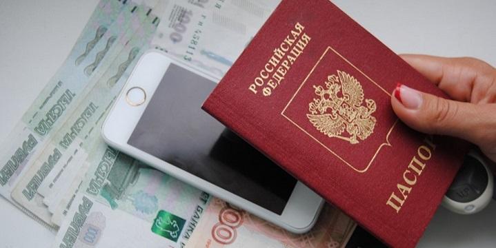 Мобильник на банкнотах и паспорт в женской руке
