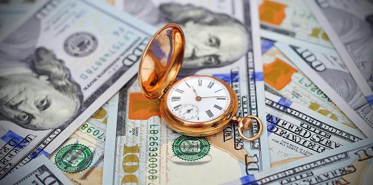 Золотые часы лежат на стодолларовых купюрах