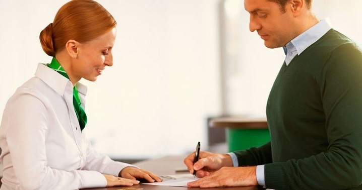 Специалист банка принимает у клиента заявление на кредит