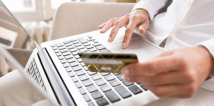 Женщина за ноутбуком с картой в руках что-то оформляет в режиме онлайн