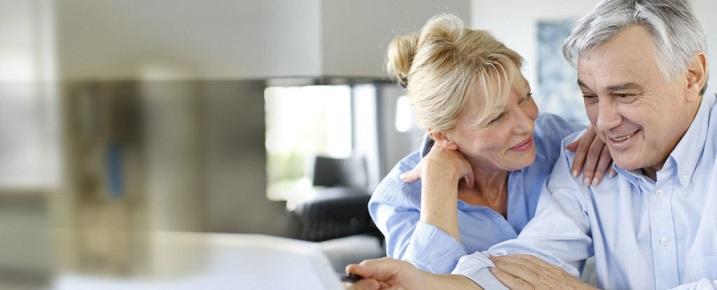 Пожилая пара рассматривает предложения за ноутбуком