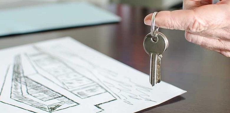 Чертеж будущего дома на столе и ключи на пальце