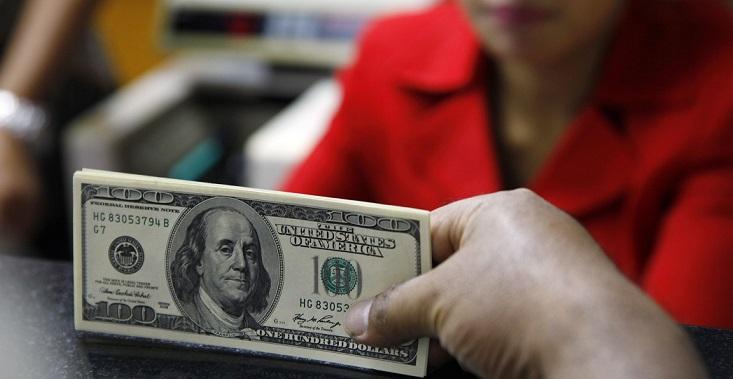 Человек получает доллары в обменнике