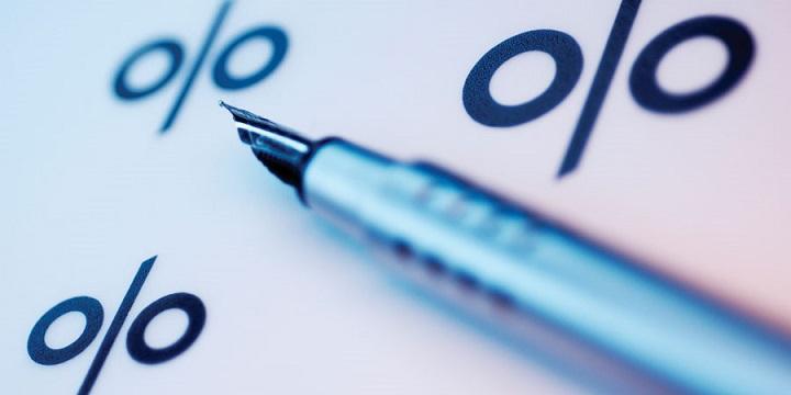 Знаки процентов на бумаге и ручка