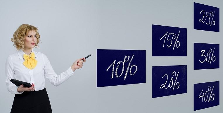 Сотрудник банка указывает на разные таблички с процентами