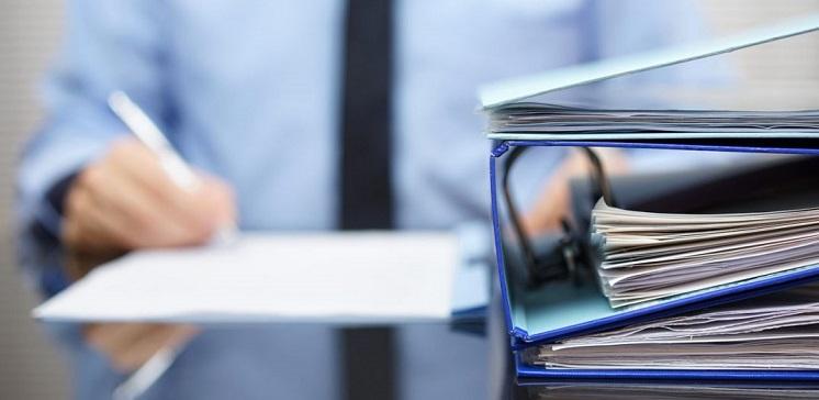 Мужчина в галстуке подписывает документы