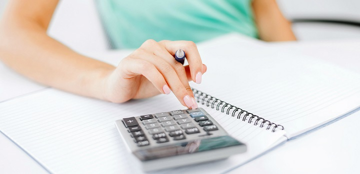 Девушка считает проценты на калькуляторе