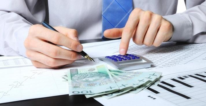 Мужчина ведет расчет причитающейся выплаты на калькуляторе