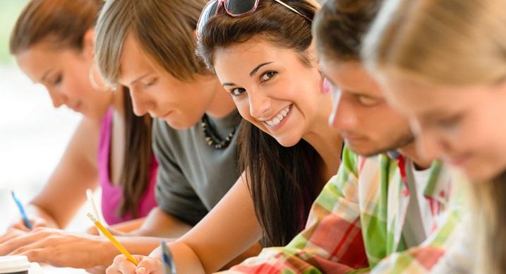 Девушка студентка смотрит в камеру и улыбается