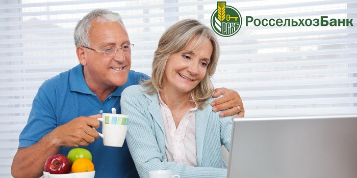 Семейная пара в возрасте изучает что-то на ноутбуке