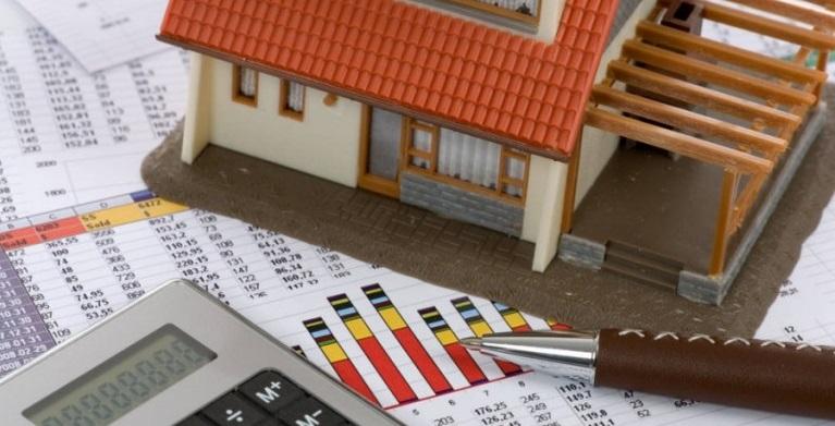 Миниатюра дома стоит на документах, рядом калькулятор и ручка