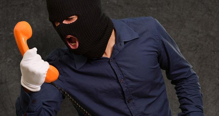 Мужчина в черной маске кричит в телефонную трубку