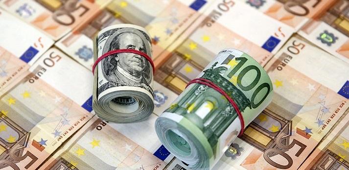Купюры по 50 евро, разложенные на столе, и роллы из 100 евро и 100 долларов поверх них
