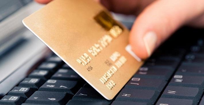 Золотистая кредитная карта в руках на клавиатуре ноутбука