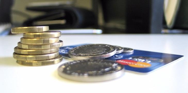 Стопка монет и кредитная карта