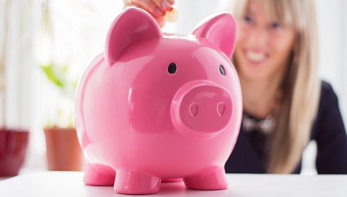 Женщина кладет в розовую копилку деньги