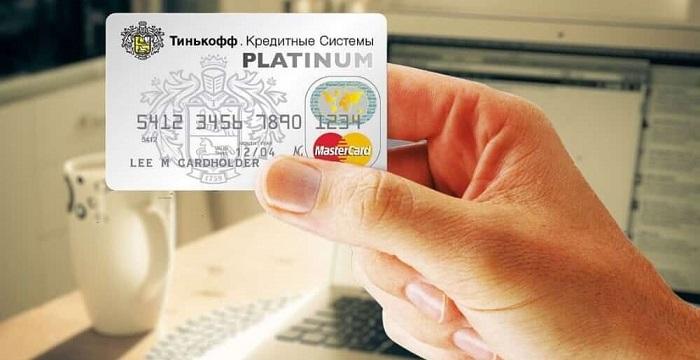 Женская рука держит кредитную карту банка Тинькофф на фоне ноутбука