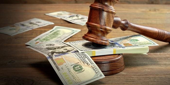 Судебный молоток на пачках стодолларовых купюр