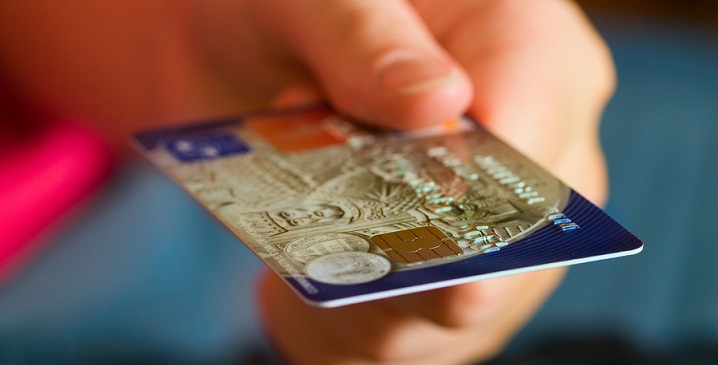 Мужская рука протягивает кредитку с постоянным предложением