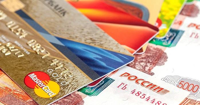Несколько банковских карт от Сбербанка лежат на пятитысячных купюрах