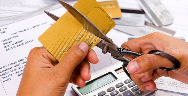 Кредитную карту перерезают ножницами