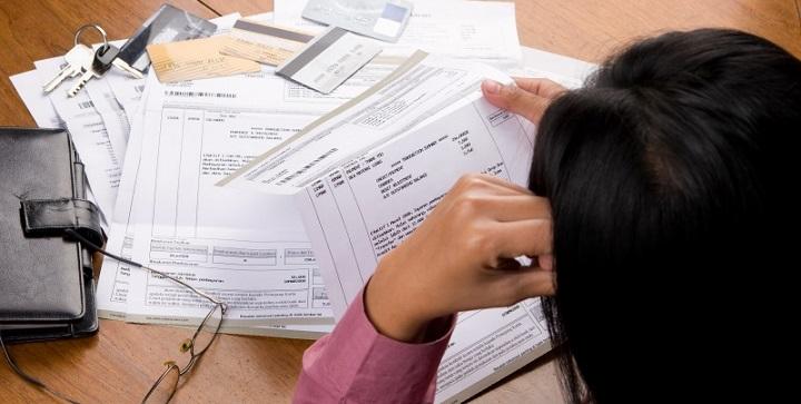 Девушка разбирает бумаги с долговыми обязательствами по картам