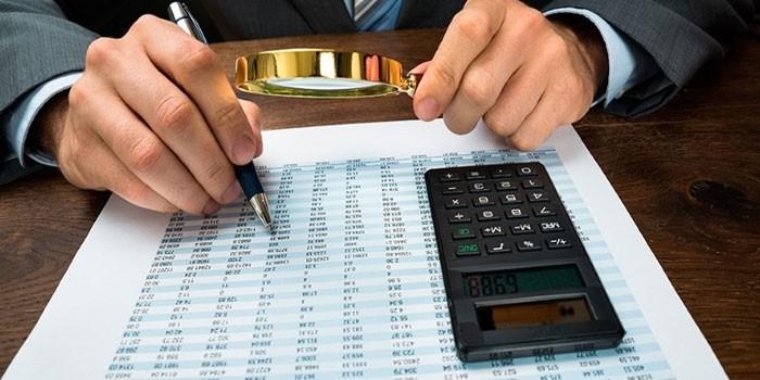 Мужчина изучает цифры на бумаге под лупой с калькулятором