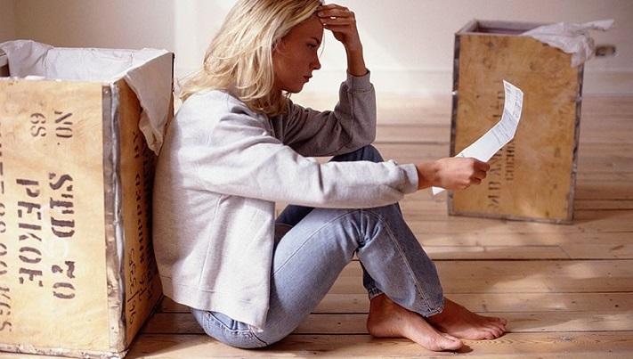 Девушка сидит на полу с собранными в коробках вещами и читает решение суда