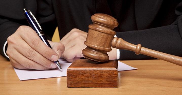 Человек пишет заявление на фоне судебного молота
