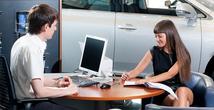 Девушка в автосалоне оформляет кредит на автомобиль