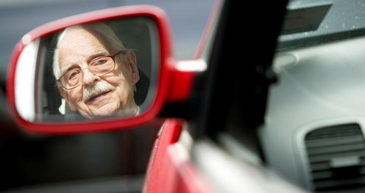 Мужчина пенсионного возраста за рулем красного автомобиля