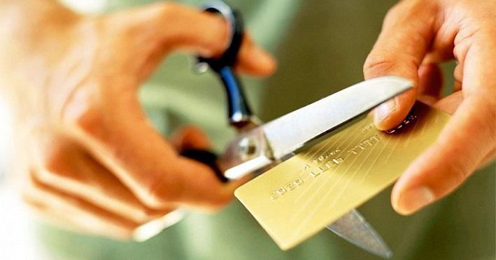 Мужчина режет ножницами кредитную карту