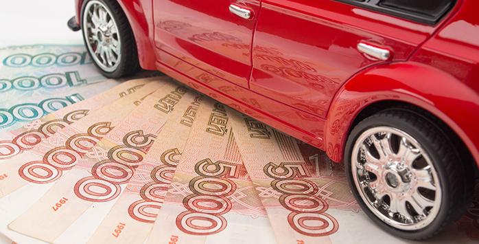 Красное игрушечное авто стоит на веере из рублевых пятитысячных банкнот