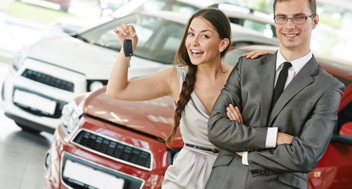 Девушка с менеджером автосалона на фоне своего нового автомобиля