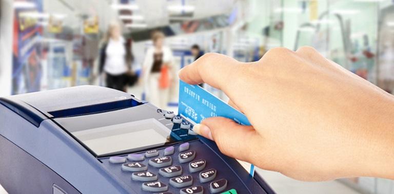 Продавец проводит картой по терминалу при совершении продажи